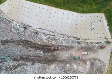 Garbage trucks unload garbage to a landfill, drone photo