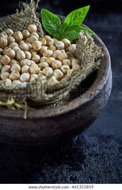 Garbanzo beans (chickpeas) with basil in clay bowl on black rustic background