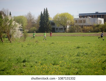 GARCHING, GERMANY - APRIL 18, 2018 -  kids playing soccer on a green field in springtime near school