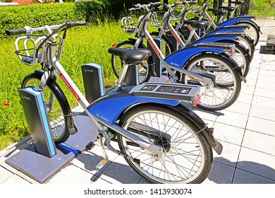 GARCHING, GERMANY - JUNE 2, 2019 eletric bikes ready to rent lined up on the sidewalk of an urban road