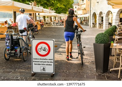 GARDA, LAKE GARDA, ITALY - SEPTEMBER 2018: Two people abiding by the requirment on the sign to dismount and push their bikes on the promenade in Garda on Lake Garda