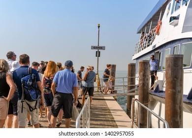 GARDA, LAKE GARDA, ITALY - SEPTEMBER 2018: Passengers queuing to board a passenger ferry at the town of Garda on Lake Garda.