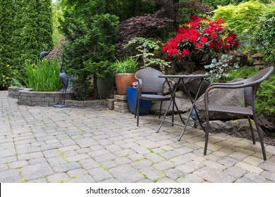 Garden backyard with lush plants landscaping pond water fountain and stone paver patio hardscape with wicker bistro furniture chair and table set spring season