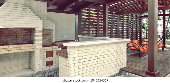 Garden Or Backyard Outdoor Pavilion With Wood Pergola, Bar Counter, Brick Oven, Fireplace And Barbecue For Cookout Food. Summer Party Place