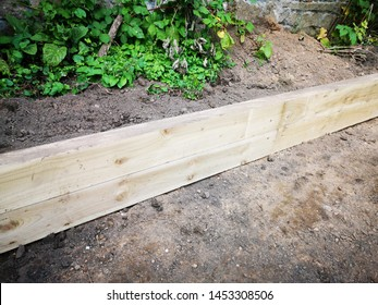 A garden being landscaped using large wooden sleepers as borders for flower and plant beds and edges of a lawn