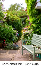 A garden bench beside an idyllic colourful summer UK cottage garden borde