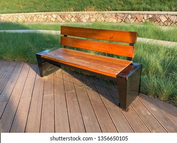 Garden bench on timber floor with green foliage background in a park for rest, Fuzhou,Fujian,China