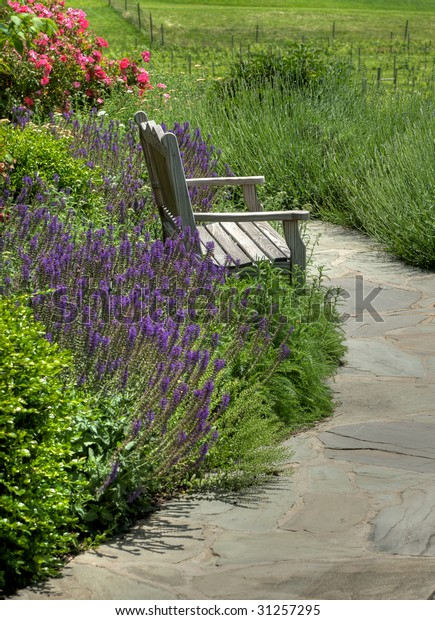 Fine Garden Bench Surrounded By Flowers Spring Stock Photo Edit Ncnpc Chair Design For Home Ncnpcorg