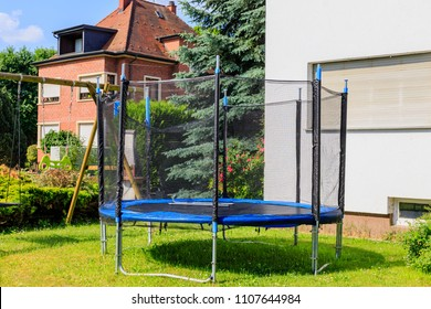 Garden big Trampoline on green grass on Playground in the yard. Outdoor Trampoline with safety net with Zipper entrance. Open Jump Trampolining.
