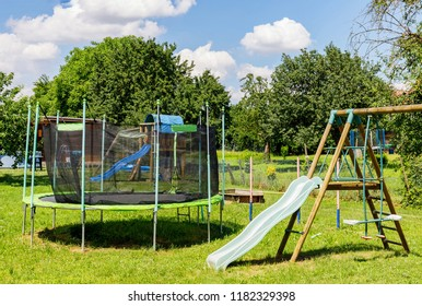 Garden big Trampoline on green grass on Playground. Outdoor Trampoline with safety net with Zipper entrance. Open Jump Trampolining.