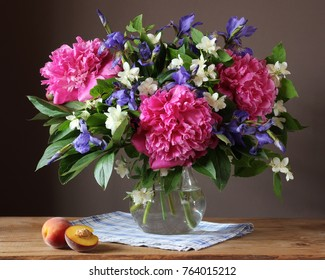 Garden bouquet of peonies, irises and Jasmine in a glass jug. Still life with flowers in a vase.