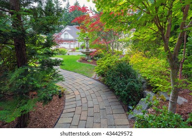 Garden brick paver path in frontyard with water fountain plants shrubs evergreen and deciduous trees landscaping