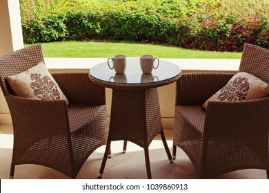 Garden brown furniture, summer day, table and two chairs, two cups on the table.