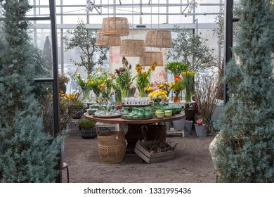 A garden center displaying different spring flowers on a table.