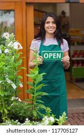 Garden center worker holding open sign at entrance to garden center