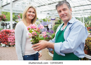 Garden center worker holding plant standing with blonde smiling woman