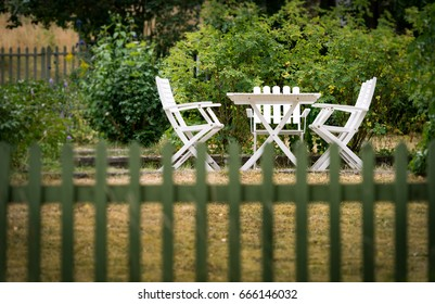 Garden chairs and table behind fence. Green grass and trees. Sweden, Europe, Scandinavia.