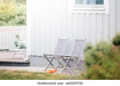 Garden chairs and white house. Green grass. Sweden, Europe, Scandinavia.