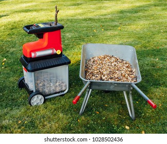 garden chipper, electric shredder (mulcher) with wheelbarrow full of wooden mulch, green grass background
