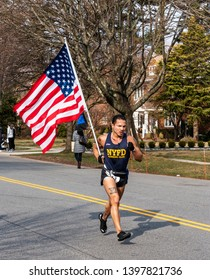 Garden City, New York, USA - 30 March 2019: A NYPD runner is racing a local 5K carrying an American Flag.