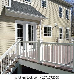 Garden deck and french doors, detail. Champagne house siding, red brown boards, white railings.