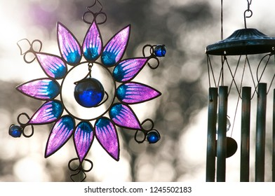 The garden decorations -  the brass  wind  chime and  glass flower of  lotus on sunset. Ireland .Dublin.