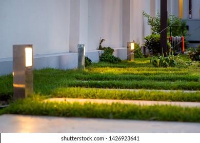 garden decorative lantern lighting marble walkway in the evening backyard with a green lawn, closeup lantern illumination warm light marble pavement.