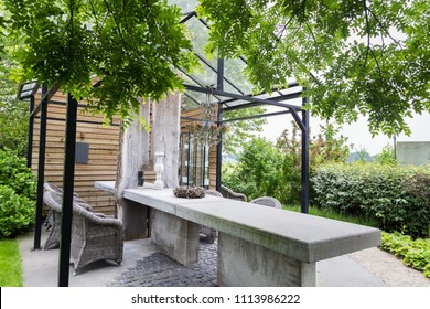 Garden design with concrete table with rooftop of a green house