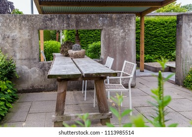 Garden design with concrete wall, window, rooftop and wooden table