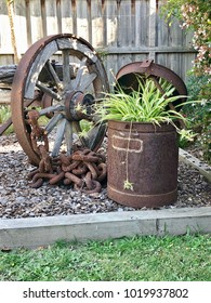 Garden display of old rustic wagon wheel and large rusty steel container with plant