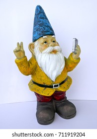 Garden dwarf with mobile phone makes peace sign  isolated on white background