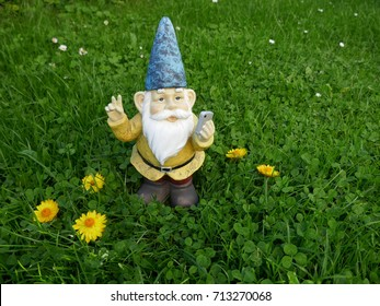 Garden dwarf with mobile phone on a green meadow makes a selfi with peace sign