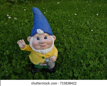 Garden dwarf with watering can and blue hat on a green meadow