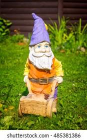 Garden dwarf with a wheelbarrow in a home garden