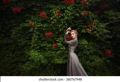 Garden of Eden. Red flowers around girl in grey dress