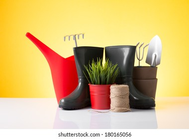 Garden equipment (boots, shovel, rake, pot) over yellow background
