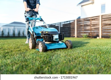 Garden equipment. Gas-push lawn mower on the green grass, male legs on background