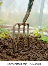 a garden fork stuck into healthy soil