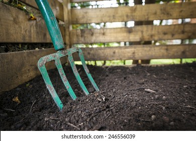 Garden fork turning black composted soil in wooden compost bin