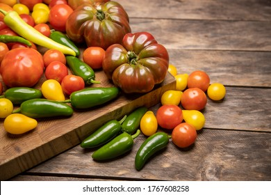 Garden fresh vegetables on wood butcher block on top wooden table