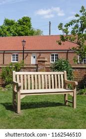 Garden furniture wooden bench in a formal Victorian English garden