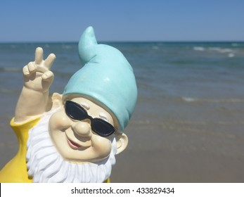 Garden gnome on vacation at sea makes peace signs against the ocean and cloudless blue sky. Baltic Sea, Schleswig-Holstein, Germany
