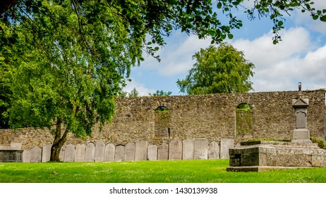 Garden of the Graveyard Abbey in the village of Athlone with ornate headstones on the wall in the background, wonderful sunny spring day  in the county of Westmeath, Ireland