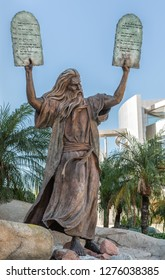Garden Grove, California, USA - December 13, 2018: Crystal Christ Cathedral. Bronze statue of Moses putting the ten commandments of two tables in the air. Some green foliage, blue sky, Cultural Center