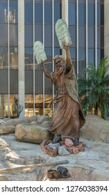 Garden Grove, California, USA - December 13, 2018: Crystal Christ Cathedral. Bronze statue of Moses putting the ten commandments of two tables in the air. Some green foliage,  Cathedral reflected.