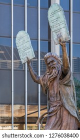 Garden Grove, California, USA - December 13, 2018: Crystal Christ Cathedral. Closeup of Bronze statue of Moses putting the ten commandments of two tables in the air. Some green foliage, Tower of hope.