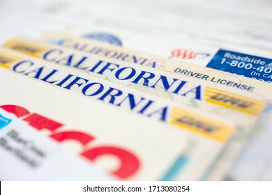 Garden Grove, California/United States - 02/06/2020: A closeup view of several California driver licenses among other wallet cards on a wooden surface.