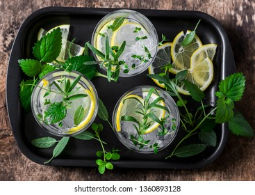 Garden herbs lemonade. Infused water with lemon, rosemary, thyme, sage and mint on wooden background, top view. Summer cool drink