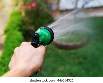 garden hose and spray gun on hand to water the green field