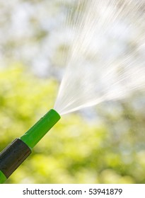 A garden hose sprays into the sunshine on a hot summer day.